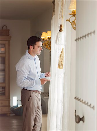 Businessman standing at window Stock Photo - Premium Royalty-Free, Code: 649-06353261