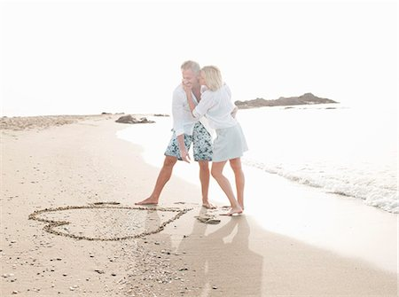 Couple drawing heart in sand on beach Stock Photo - Premium Royalty-Free, Code: 649-06353276