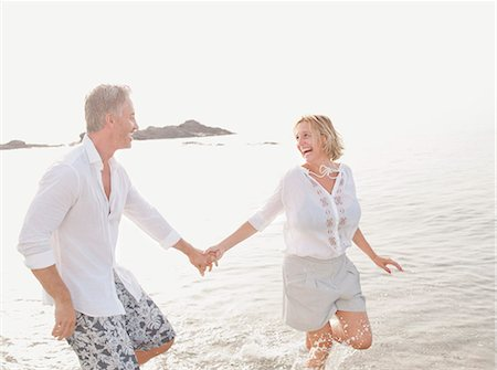 Couple playing in waves on beach Stock Photo - Premium Royalty-Free, Code: 649-06353279