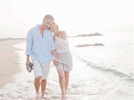 Couple walking in waves on beach Stock Photo - Premium Royalty-Free, Code: 649-06353270