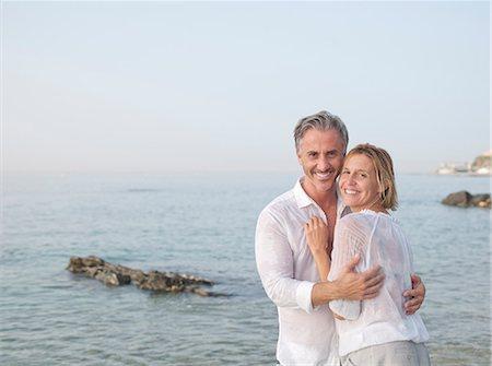 Smiling couple hugging on beach Stock Photo - Premium Royalty-Free, Code: 649-06353282
