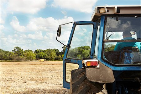 Farmer sitting in tractor in crop field Stock Photo - Premium Royalty-Free, Code: 649-06353297