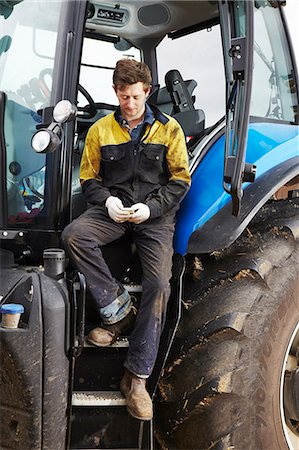 farm phone - Farmer using cell phone on tractor Stock Photo - Premium Royalty-Free, Code: 649-06353322