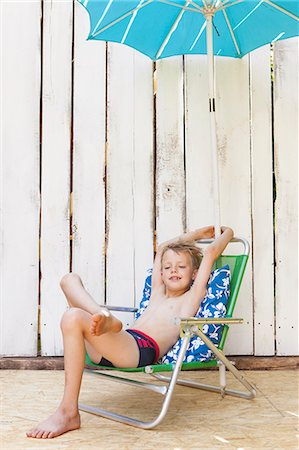 Boy in swimsuit in lawn chair indoors Stock Photo - Premium Royalty-Free, Code: 649-06353343