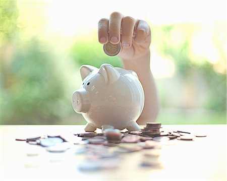 Hang putting coins in piggy bank Stock Photo - Premium Royalty-Free, Code: 649-06400384