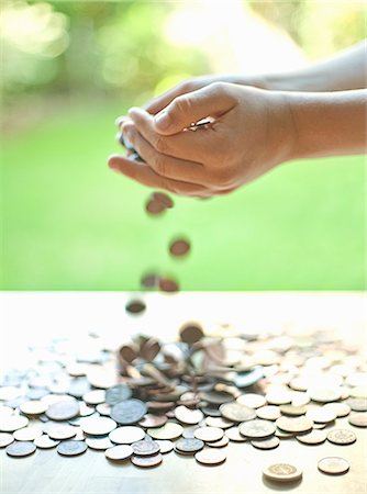 Hands pouring change on table Stock Photo - Premium Royalty-Free, Code: 649-06400387