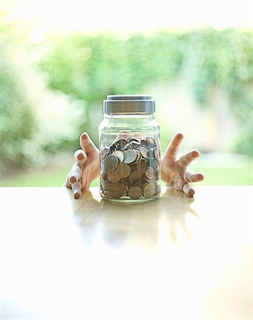 Hands grabbing jar of change Stock Photo - Premium Royalty-Free, Code: 649-06400381