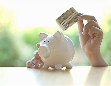savings - Hang putting dollar bill in piggy bank Stock Photo - Premium Royalty-Free, Code: 649-06400382