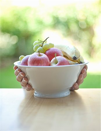 reaching - Hands holding bowl of fruit Stock Photo - Premium Royalty-Free, Code: 649-06400390