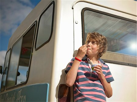 Boy eating ice cream by truck Stock Photo - Premium Royalty-Free, Code: 649-06400392