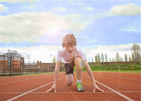 race track (people) - Boy crouched at starting line on track Stock Photo - Premium Royalty-Free, Code: 649-06400417