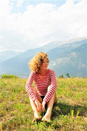Woman sitting on rural hilltop Stock Photo - Premium Royalty-Free, Code: 649-06400483