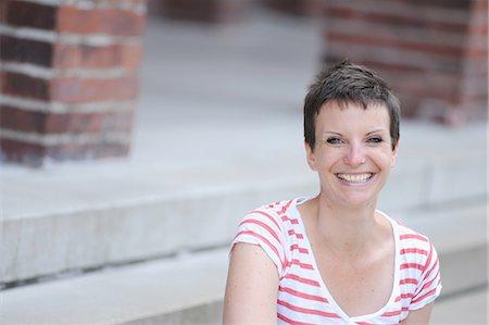 short hair - Smiling woman sitting on city street Stock Photo - Premium Royalty-Free, Code: 649-06400672