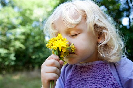 smelling - Girl smelling wildflowers outdoors Stock Photo - Premium Royalty-Free, Code: 649-06400729