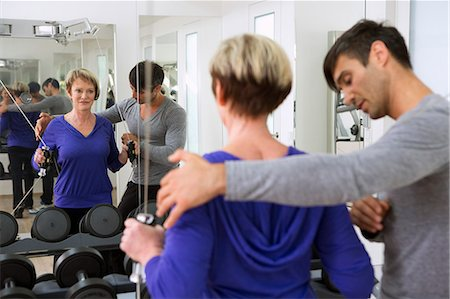 fitness older women gym - Trainer adjusting woman's form in gym Stock Photo - Premium Royalty-Free, Code: 649-06400819
