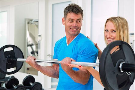 fitness   mature woman - Trainer adjusting man's form in gym Stock Photo - Premium Royalty-Free, Code: 649-06400822