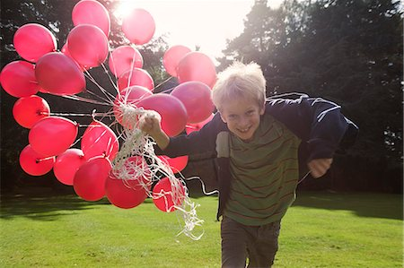 preteen  smile  one  alone - Boy carrying bunch of balloons outdoors Stock Photo - Premium Royalty-Free, Code: 649-06400834