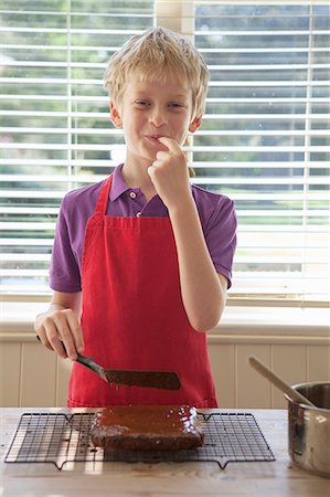 Boy tasting cake frosting in kitchen Stock Photo - Premium Royalty-Free, Code: 649-06400847