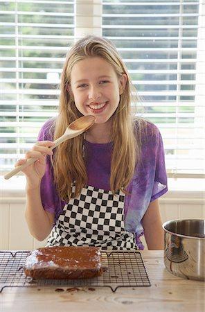 preteen girl licking - Girl tasting cake frosting in kitchen Stock Photo - Premium Royalty-Free, Code: 649-06400849