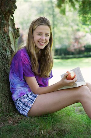 preteen  smile  one  alone - Girl eating apple and reading in park Stock Photo - Premium Royalty-Free, Code: 649-06400854