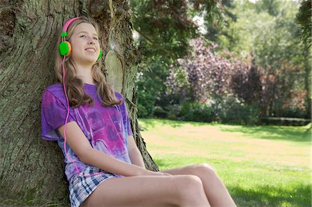 entertainment - Girl listening to headphones in park Stock Photo - Premium Royalty-Free, Code: 649-06400855