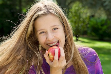 preteen open mouth - Smiling girl eating apple in park Stock Photo - Premium Royalty-Free, Code: 649-06400857