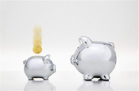 Coin dropping into smaller piggy bank Stock Photo - Premium Royalty-Free, Code: 649-06400872