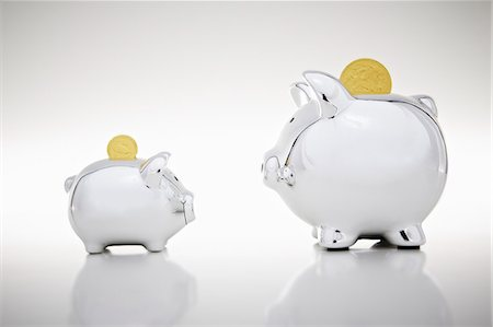 Gold coins dropping into piggy banks Stock Photo - Premium Royalty-Free, Code: 649-06400881