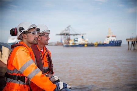 Workers on tug boat overlooking ocean Stock Photo - Premium Royalty-Free, Code: 649-06400905