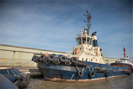 property release - Tug boat docked in urban harbor Stock Photo - Premium Royalty-Free, Code: 649-06400924