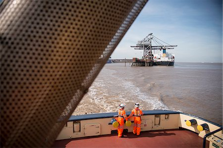 ships at sea - Workers on tug boat overlooking crane Stock Photo - Premium Royalty-Free, Code: 649-06400920
