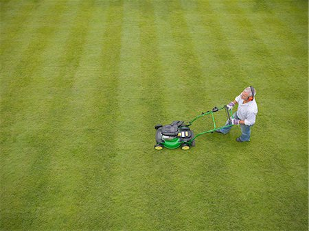 Man wearing headphones and mowing lawn Stock Photo - Premium Royalty-Free, Code: 649-06400994