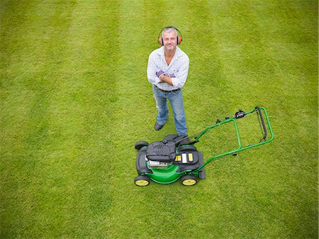 Man standing with lawn mower Stock Photo - Premium Royalty-Free, Code: 649-06400995