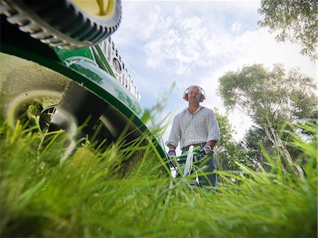 Low angle view of man mowing lawn Stock Photo - Premium Royalty-Free, Code: 649-06400999