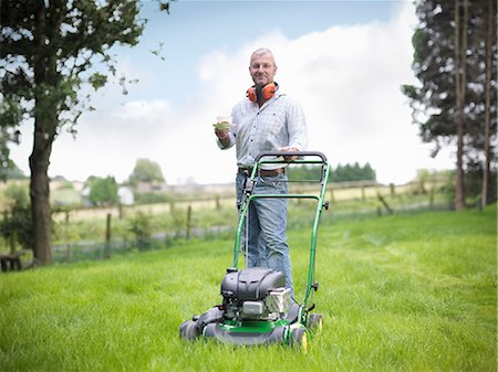 Man with lawn mower having cup of tea Stock Photo - Premium Royalty-Free, Code: 649-06401004