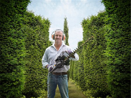Man holding hedge trimmer in garden Stock Photo - Premium Royalty-Free, Code: 649-06401007