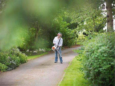Man blowing leaves on paved road Stock Photo - Premium Royalty-Free, Code: 649-06401008
