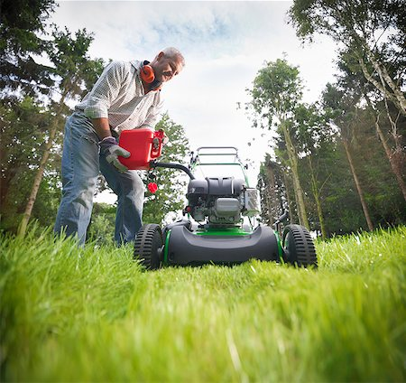 Man pouring gas into lawn mower Stock Photo - Premium Royalty-Free, Code: 649-06401002