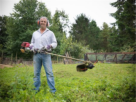 Man trimming weeds in garden Stock Photo - Premium Royalty-Free, Code: 649-06401011