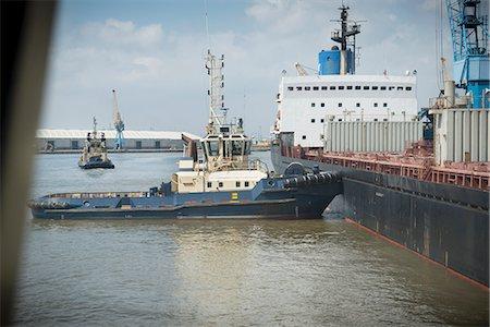 property release - Tugboat pushing ship in urban harbor Stock Photo - Premium Royalty-Free, Code: 649-06401050
