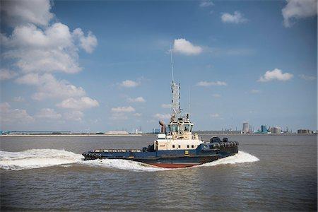 property release - Tugboat sailing in urban harbor Stock Photo - Premium Royalty-Free, Code: 649-06401051