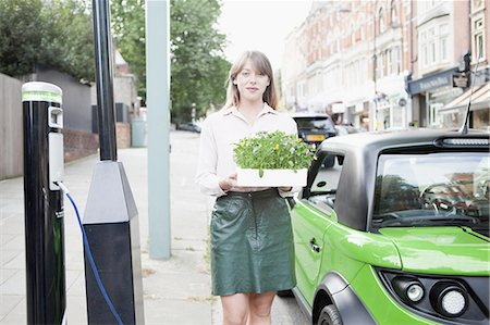 Woman carrying flowerbox on city street Stock Photo - Premium Royalty-Free, Code: 649-06401125