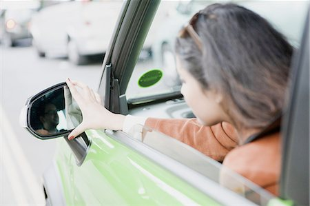 Woman adjusting side mirrors Stock Photo - Premium Royalty-Free, Code: 649-06401140
