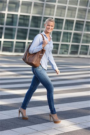 Smiling woman crossing city street Stock Photo - Premium Royalty-Free, Code: 649-06401195
