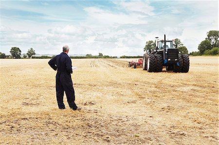 plow - Farmer overlooking tractor in crop field Stock Photo - Premium Royalty-Free, Code: 649-06401212