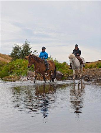 Boys riding horses through creek Stock Photo - Premium Royalty-Free, Code: 649-06401342