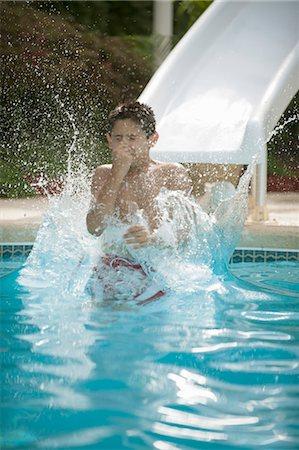 Boy on water slide splashing into pool Stock Photo - Premium Royalty-Free, Code: 649-06401431