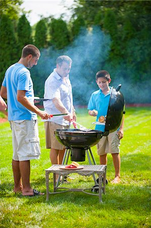 Father and sons grilling outdoors Stock Photo - Premium Royalty-Free, Code: 649-06401460