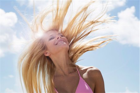 Smiling woman tossing her hair Stock Photo - Premium Royalty-Free, Code: 649-06432241