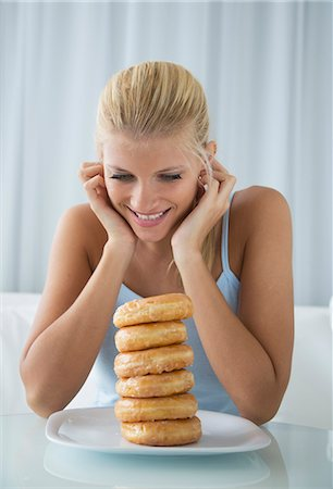 Woman admiring stack of donuts Stock Photo - Premium Royalty-Free, Code: 649-06432252
